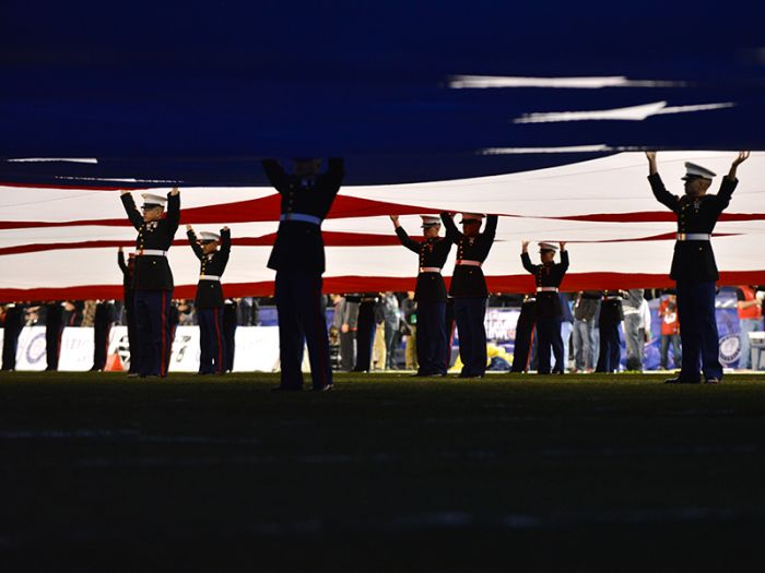 U.S. Marines hold up the U.S. flag on the field at Qualcomm Stadium.
